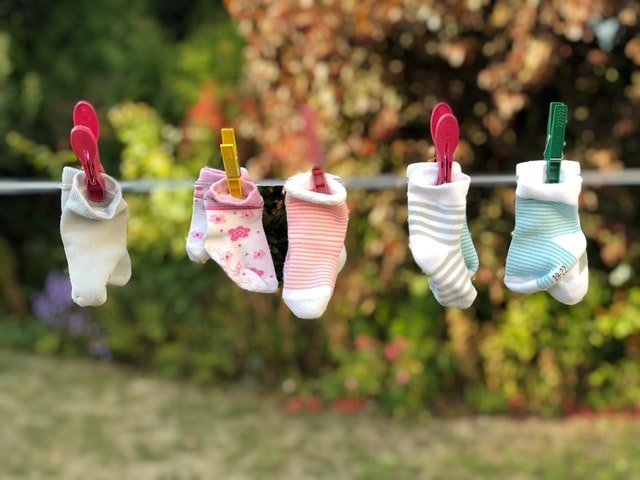oseline-with-pairs-of-baby-socks-clipped-to-it-min.jpg